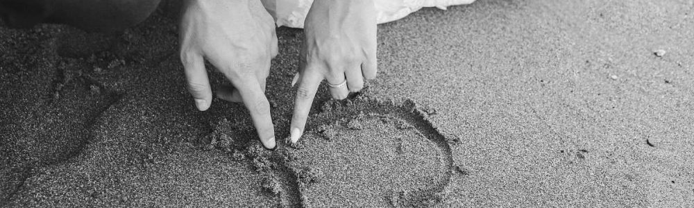 black-and-white-grayscale-photography-of-man-and-woman-draw-heart-on-sand-grey-grey-image